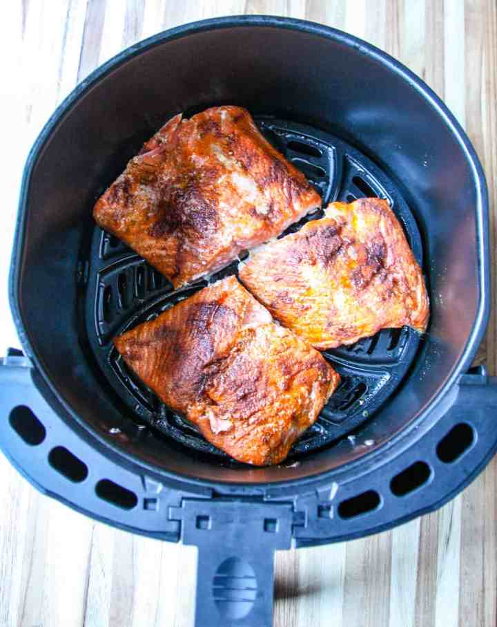 Three cooked salmon fillets in an air fryer basket.