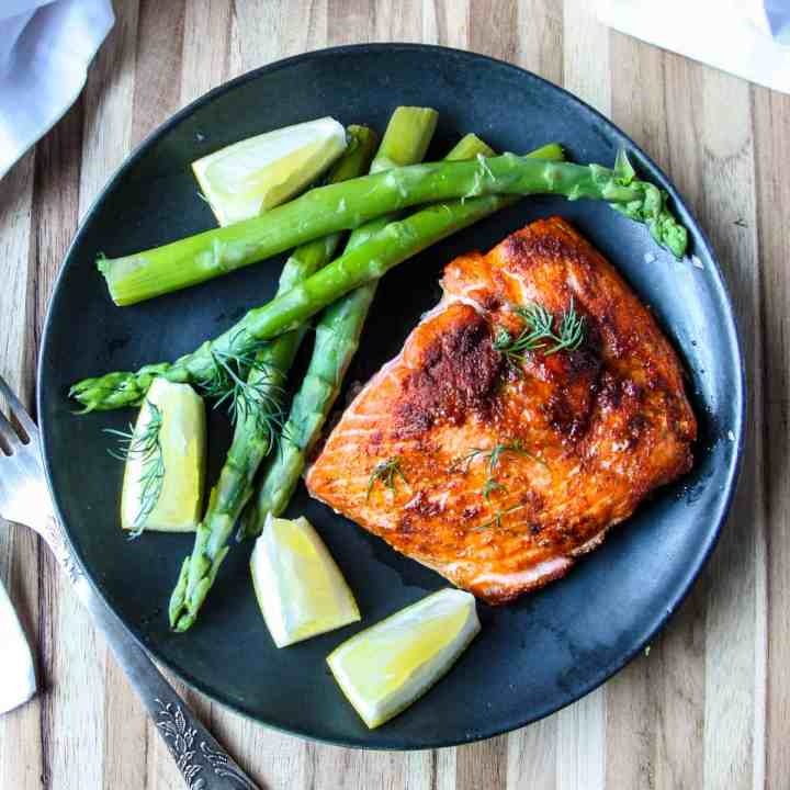 An air fryer cooked fillet of salmon on a black plate with asparagus and lemon wedges.