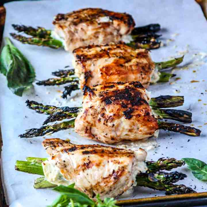 Grilled chicken stuffed with asparagus on a tray.