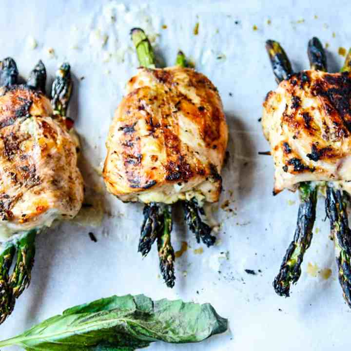Three grilled asparagus stuffed chicken breasts on a tray.