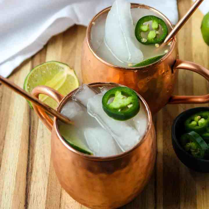 Two Mexican Mule cocktails in copper mugs garnished with lime.