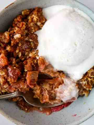 A bowl of rhubarb crisp topped with a scoop of vanilla ice cream.
