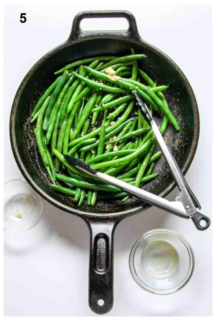 Garlic and seasonings being added to green beans in a cast iron pan.