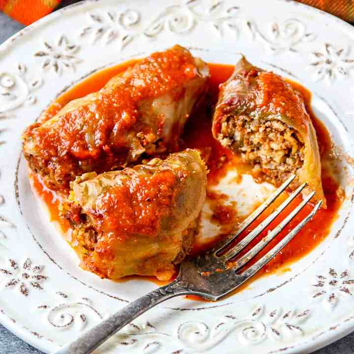 Stuffed Cabbage Rolls on a white plate with a fork.