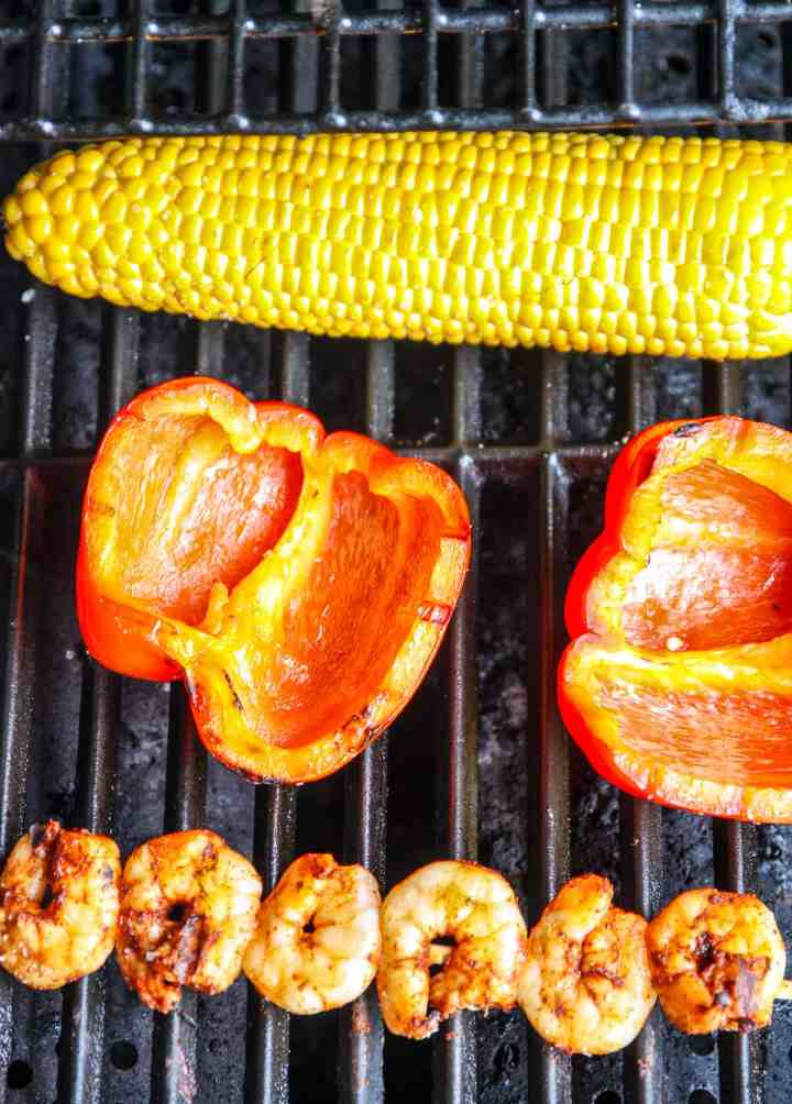 A cob of corn, a red bell pepper, and a skewer of shrimp on a grill.