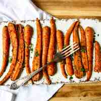 Air fried carrots on a white platter with a fork.