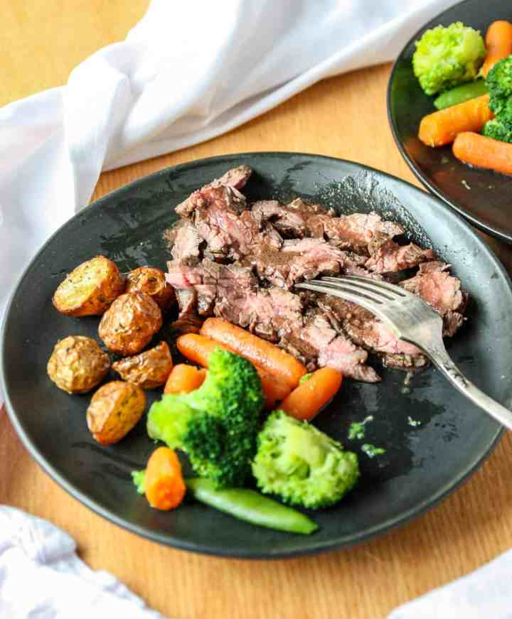 Sliced flank steak and roasted vegetables on a black plate with a fork.