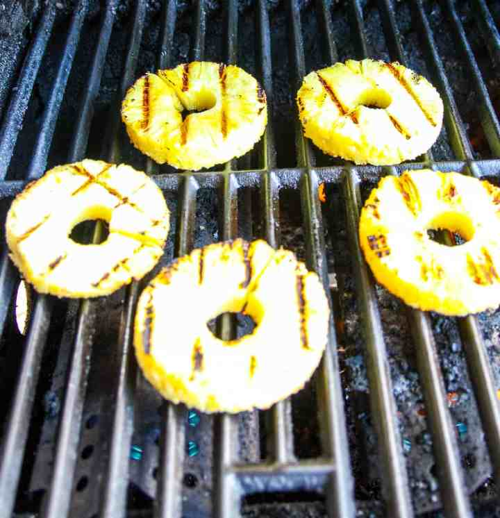 Pineapple slices cooking on a gas grill.