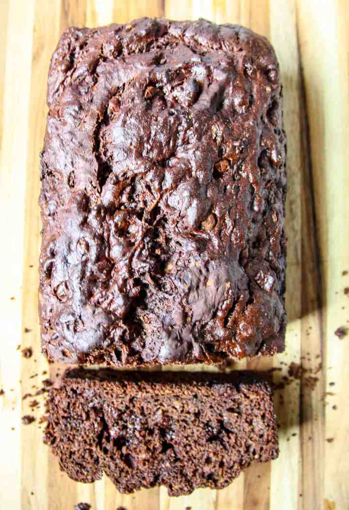 A loaf of gluten-free chocolate zucchini bread with a slice cut.