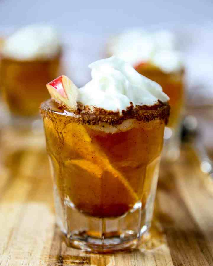 An apple pie shooter topped with whipped cream.