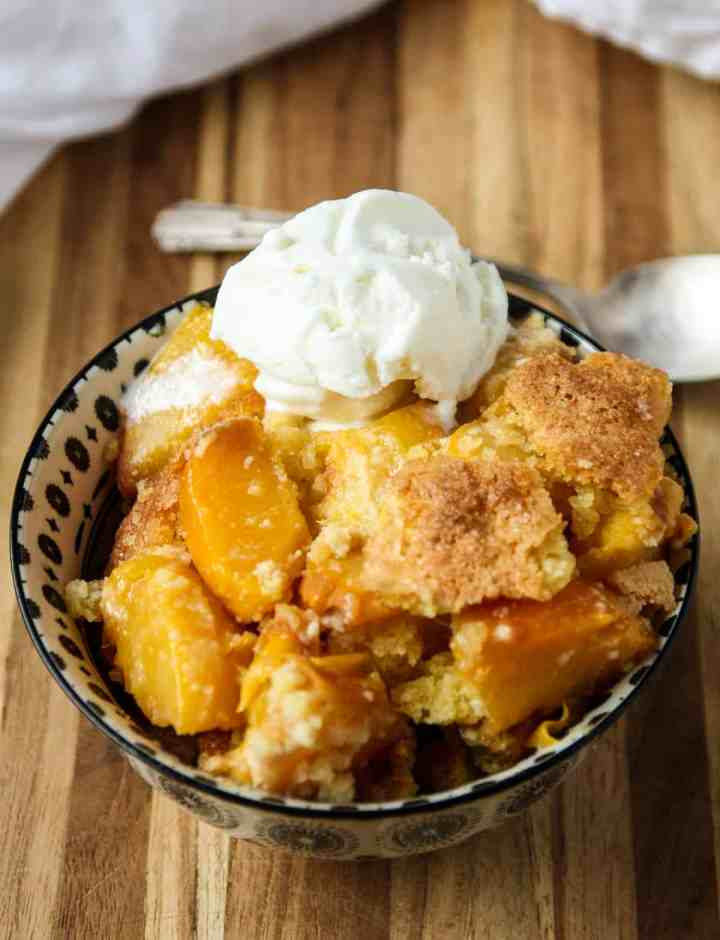 Peach cobbler topped with a scoop of ice cream in a black and white dish.