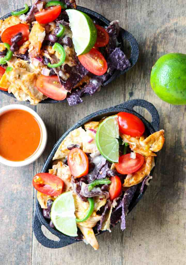 Two dishes of leftover turkey natchos with lime wedges.