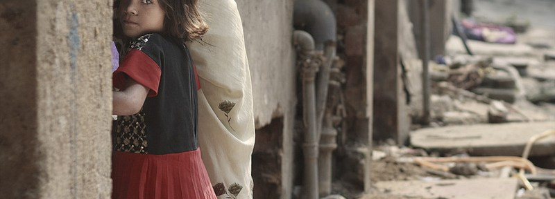 A girl stands in the street in the Indian city of Dehli