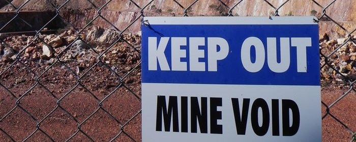 A sign attached to a fence of a mine reads 'Keep Out, Mine Void'