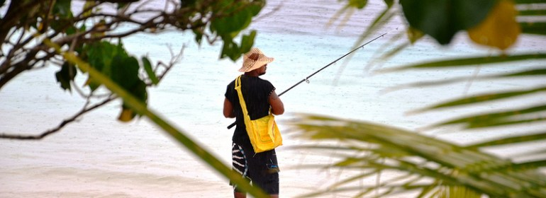 Local out fishing for the family dinner on the beach in Savaii, Samoa