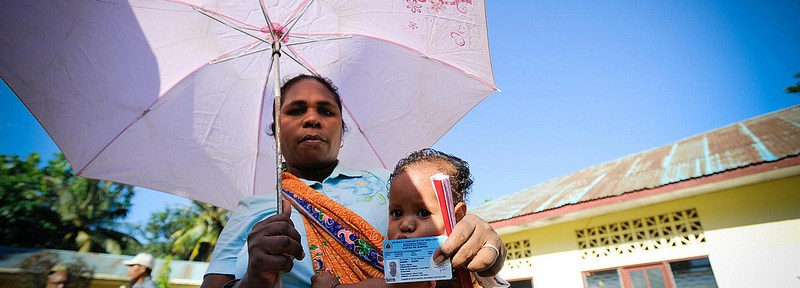 A woman shows her voter registration card at a polling station in Timor-Leste, where she is waiting to cast her vote in today's presidential run-off.
