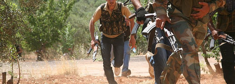 """Syrian rebels from the """"Al-Qasas Brigade"""" or """"Justice Brigade"""" run through an olive grove to avoid Syrian Army snipers as they travel between villages on foot in the northwestern Jabal al-Zawiya area."""