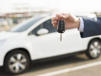 businessman-with-keys-front-car