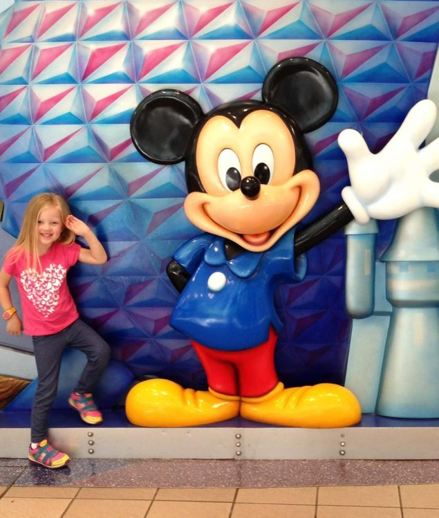 little girl posing next to mickey mouse statue at airport
