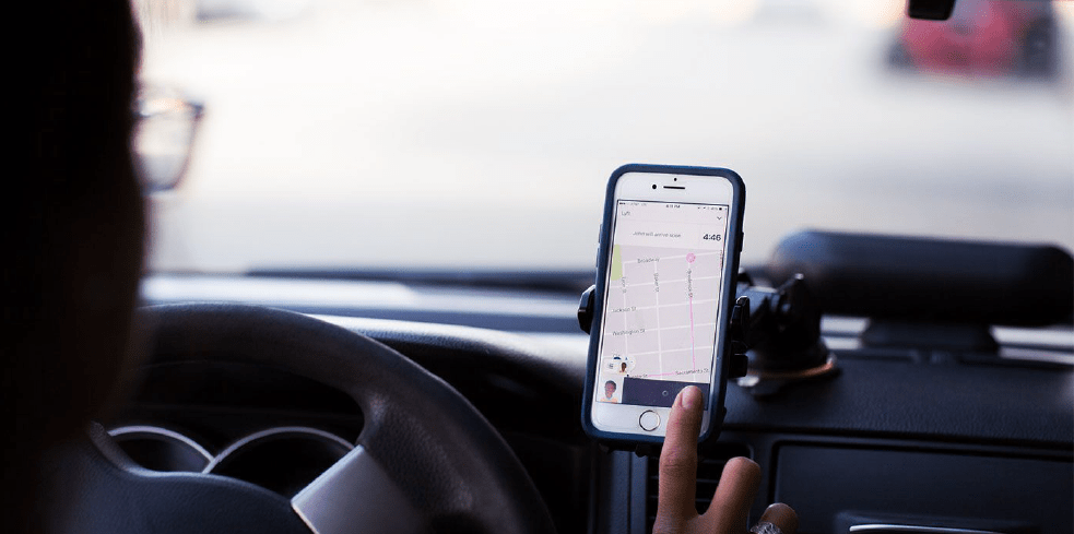 mobile phone held on dashboard of car