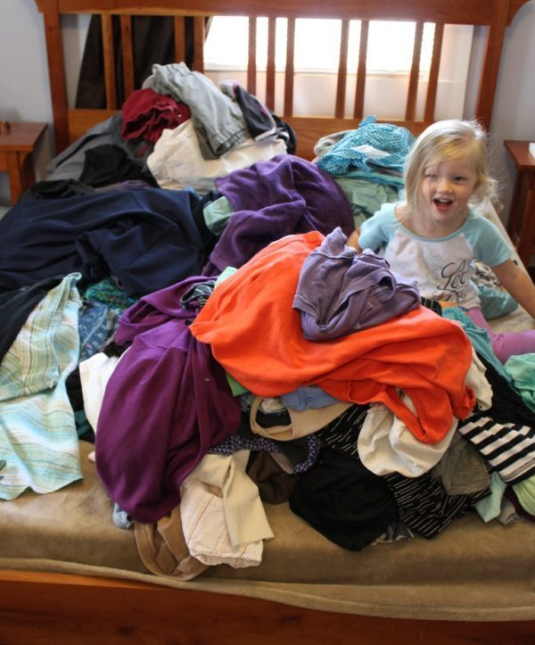 little girl on a bed with a pile of clothes