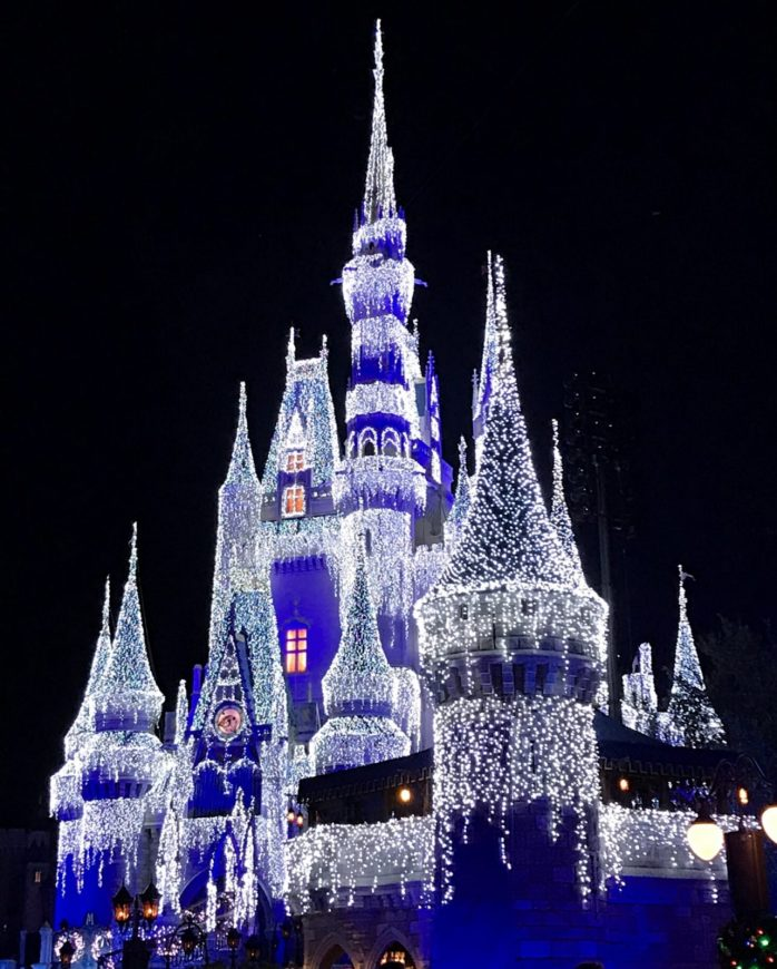 Cinderella's castle lit up at night with holiday lights