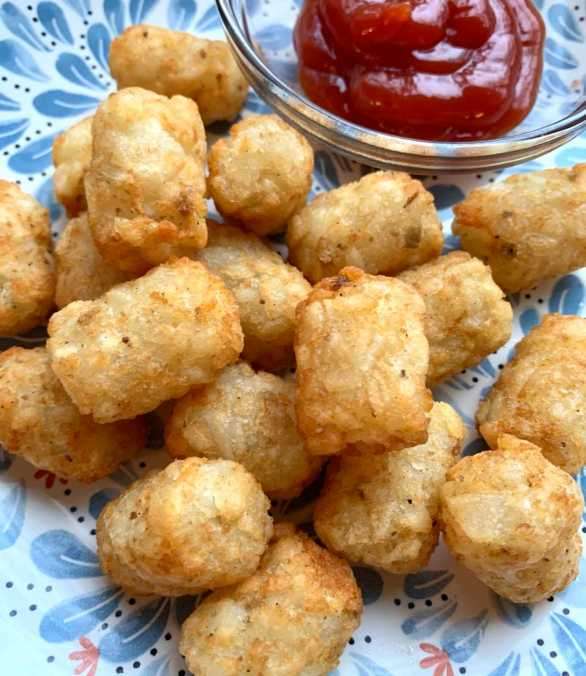 air fryer tater tots on a plate with ketchup