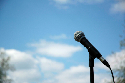 A microphone framed against a sky with clouds.