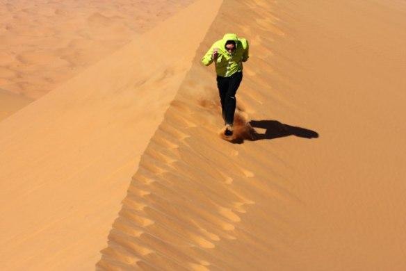 man running on sahara desert sand dunes
