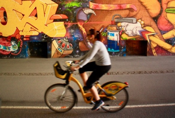 A cyclist on a Helsinki city bike goes past some cool street art