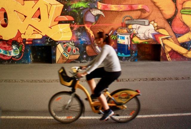 A cyclist on a Helsinki city bike goes past some cool street art