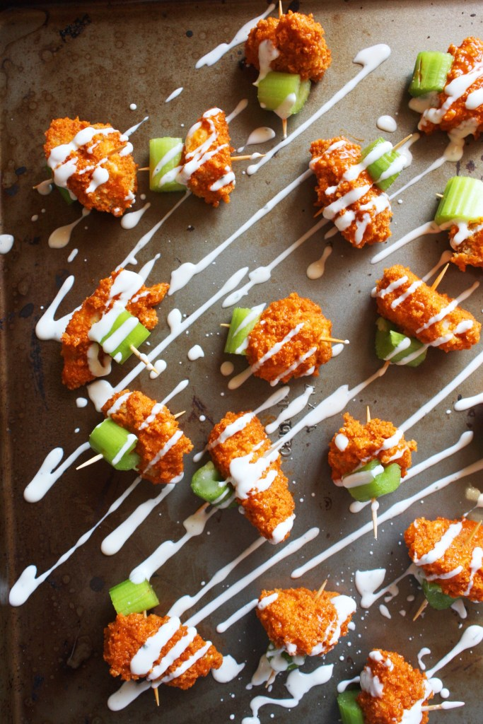 Baked Buffalo Chicken Bites - A lightened up, healthier take on the classic game day appetizer! Crispy baked bites of chicken tossed in tangy buffalo sauce, paired with celery, and drizzled with creamy ranch dressing! -- TheGarlicDiaries.com