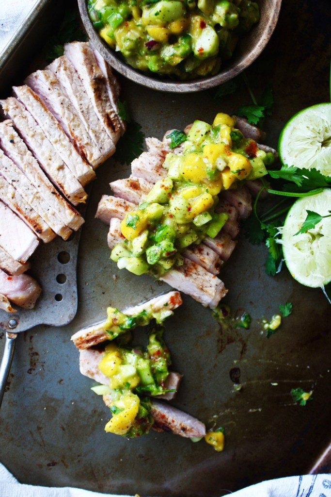 Flavor Bomb Pork Chops with Mango Salsa - This marinated pork is mouthwatering on its own, but add some delicious mango salsa on top, and you have an unforgettable meal! #glutenfree TheGarlicDiaries.com