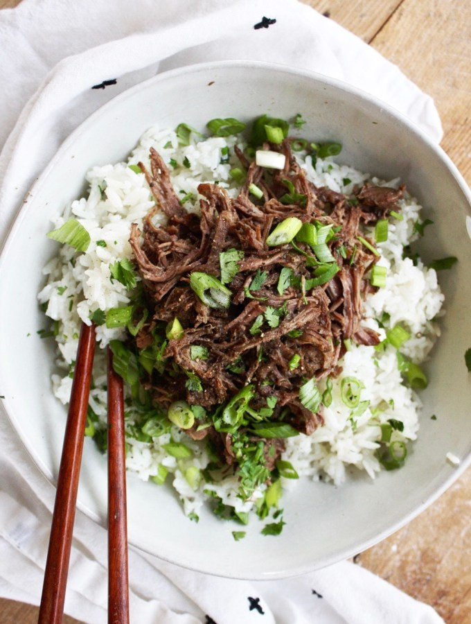 Crock Pot Korean Beef Bowls - The meat is loaded with delicious Korean flavor and is melt-in-your-mouth tender, the rice is cooked to perfection and then stirred together with coconut milk and cilantro, and the combo of the two is PERFECTION. TheGarlicDiaries.com