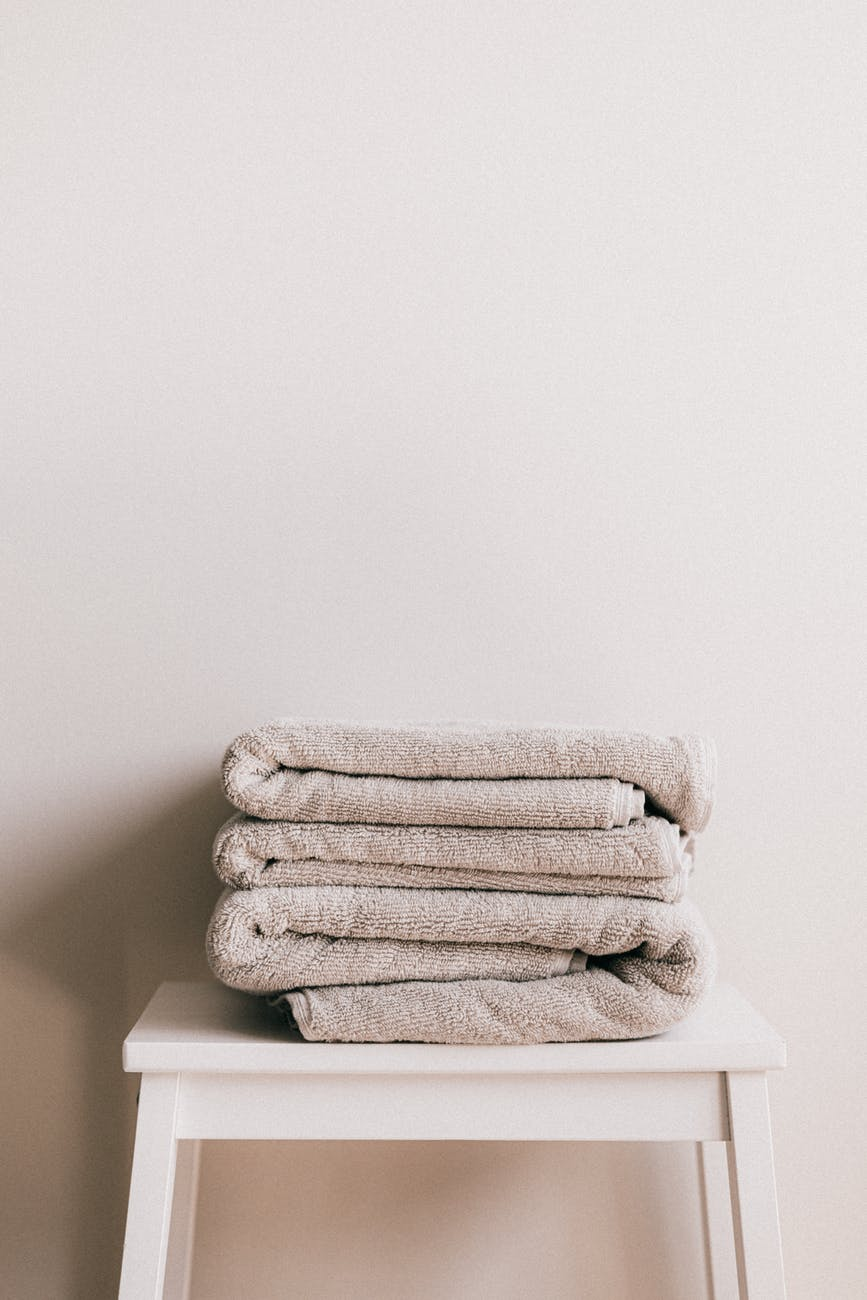 stack of fresh gray towels on white stool