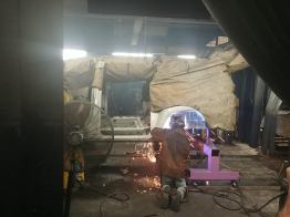 Metalworkers then cut the entire floor out of the van from about the B-pillar back.