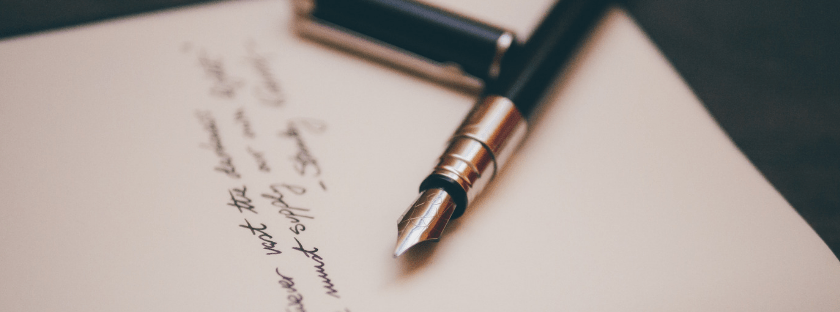 fountain pen on a notebook with writing on it