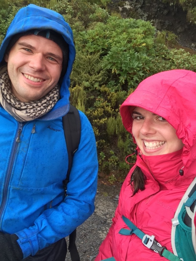 a guys and a girl smiling in raincoats