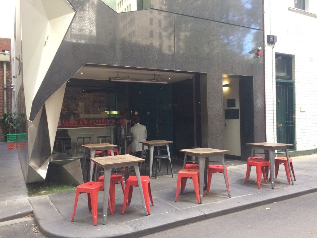 red stools outside a modern coffee shop
