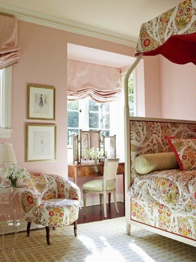 Pink walls in girls bedroom with canopy bed dressed in bold French country linens.