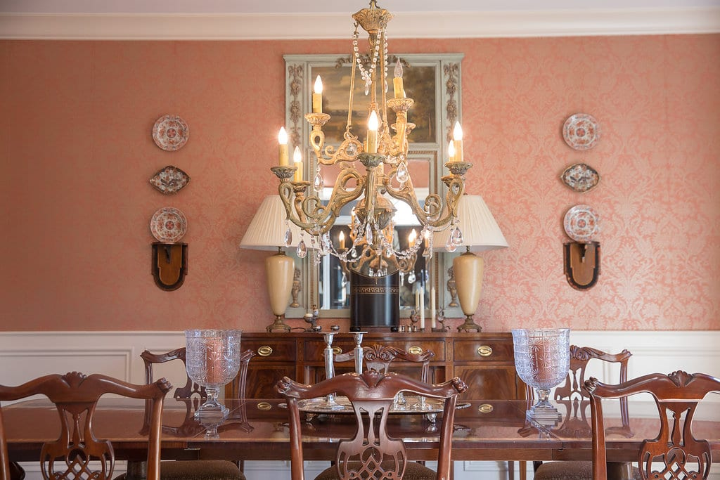 coral damask wallpaper dining room chippendale chairs chandelier hanging plates on wall antique sideboard