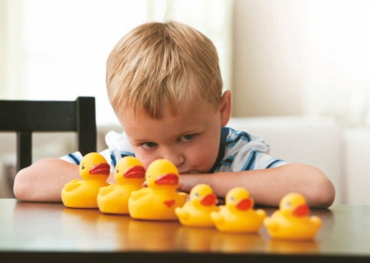 Child arranging ducks by size. Copyright Autistica