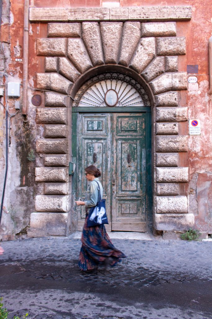 Roman woman walking in front of a door, Trastevere, Rome, Italy