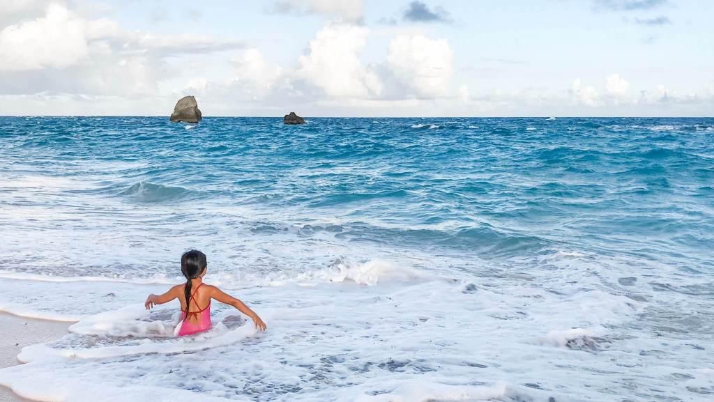 Girl sitting on beach in ocean waves in Bermuda