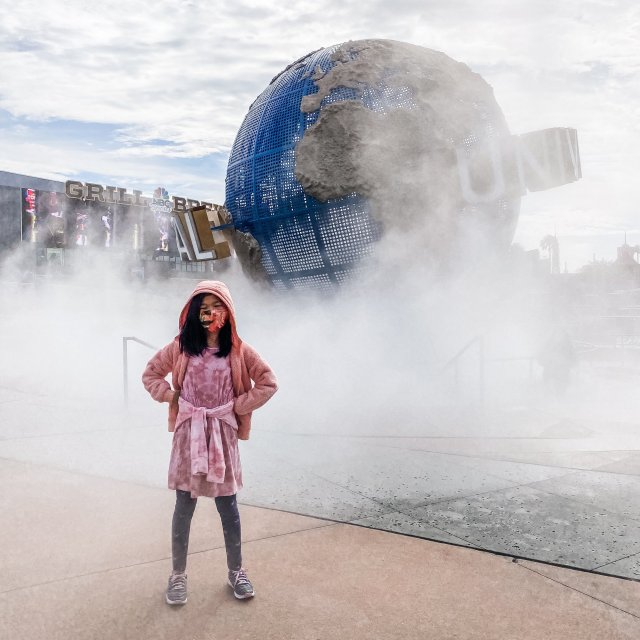 Girl standing in front of fog and Universal Studios sign in Orlando, Florida
