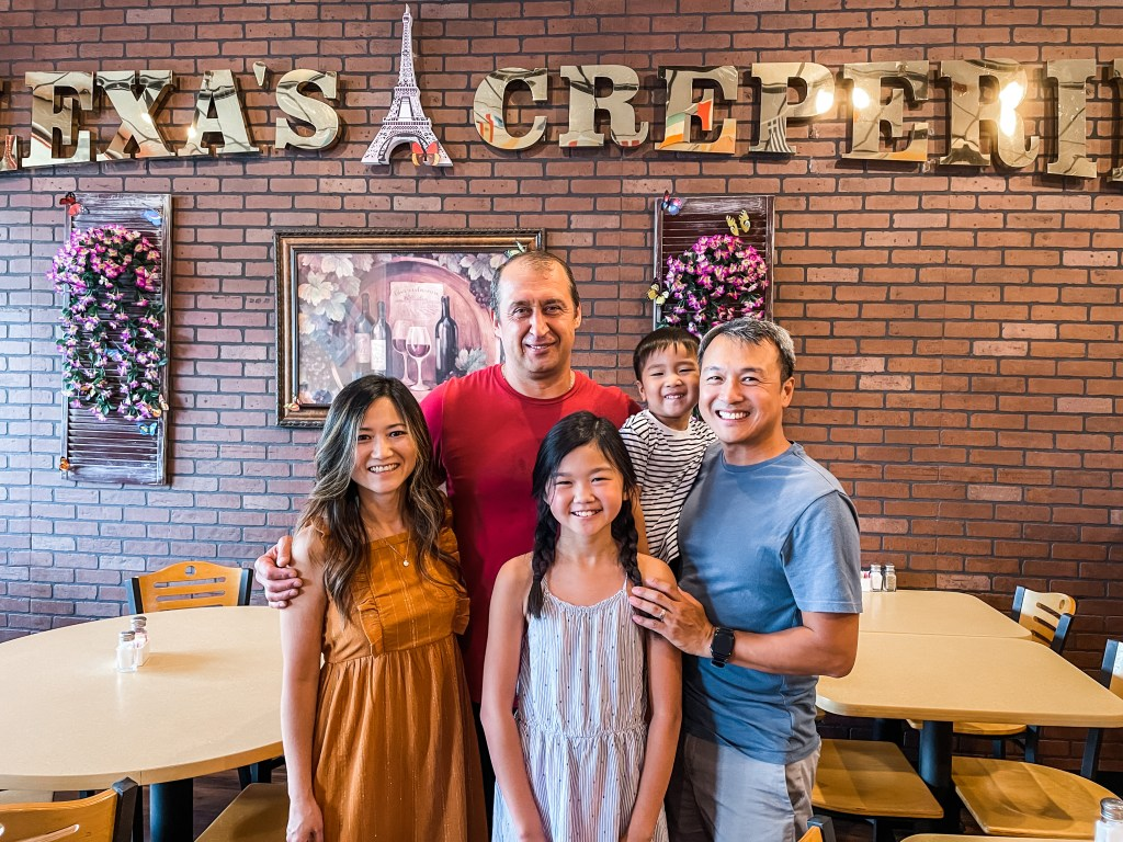 The owner of Alexa's Creperie, Sergey, taking a photo with The Globetrotting Family