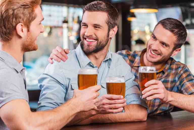 Three happy young men in casual wear talking and drinking beer while sitting at the bar counter together
