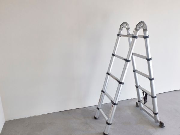 Foldable chrome stepladder against blank wall indoors.