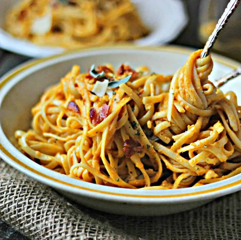 Pumpkin pasta with bacon in a white bowl