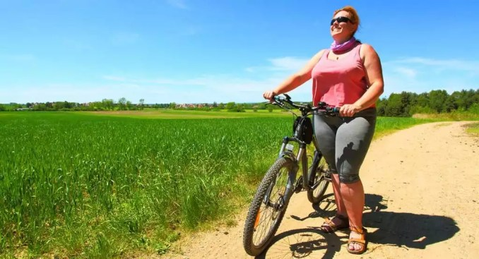 Woman overweight exercising outside with a bike